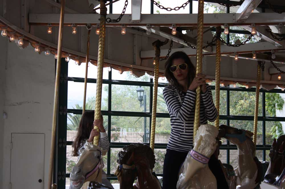 Riding the carousel with flair. And Elvis glasses.